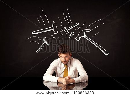 Young depressed businessman sitting under white drawn beating hammer marks