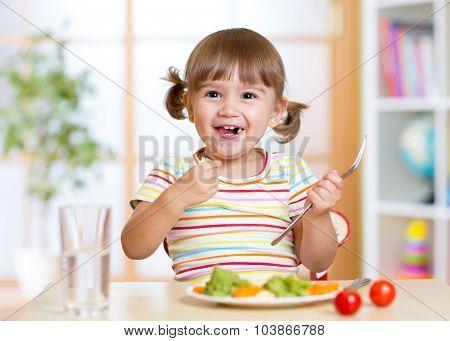 kid girl eating healthy vegetables