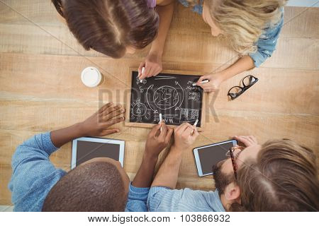Overhead view of people writing business terms on slate at table