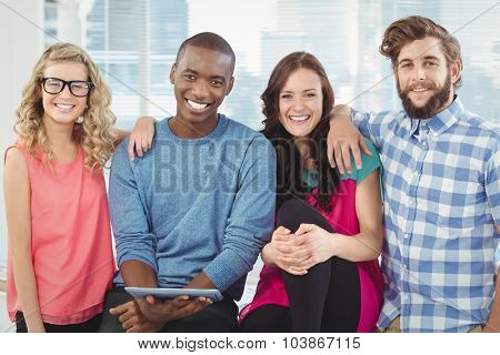 Portrait of cheerful business people with man holding digital tablet in office