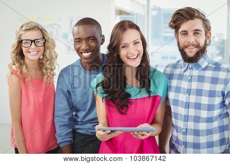 Portrait of happy business professionals using digital tablet in creative office
