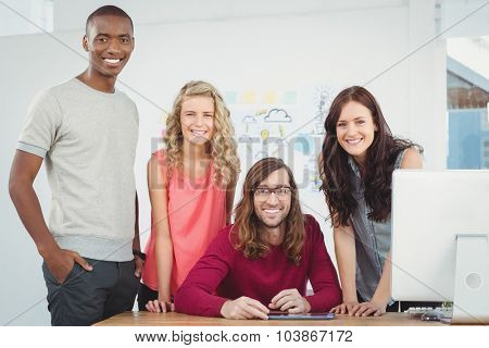 Portrait of smiling business team working at computer desk in office