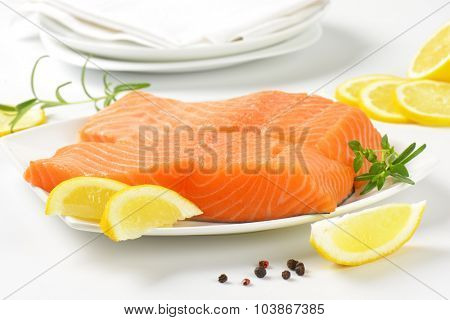 close up of raw salmon fillets on white plate
