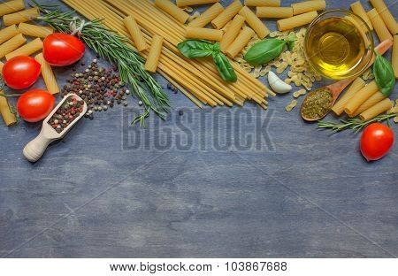 Different Pasta, Condiment, Cheese, Olive Oil And Tomatoes On Dark Wooden Background