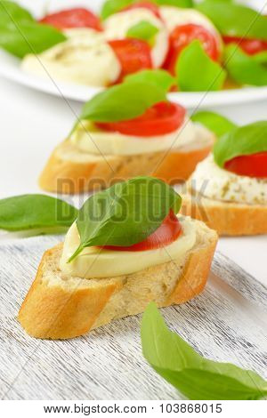 close up of mozzarella sandwiches on wooden cutting board