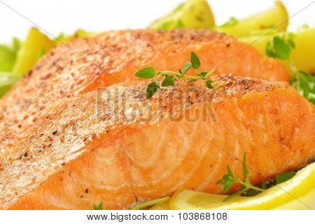 detail of pan fried salmon fillets served with vegetable garnish
