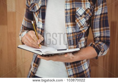 Mid section of hipster writing with pencil on book against wooden wall