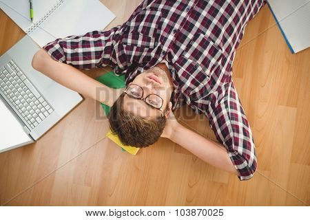 Portrait of hipster wearing eye glasses lying with hands behind head on hardwood floor