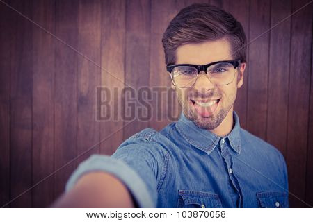 Portrait of hipster sticking out tongue against wooden wall