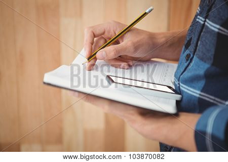 Cropped image of businessman writing with pencil on book against wooden wall