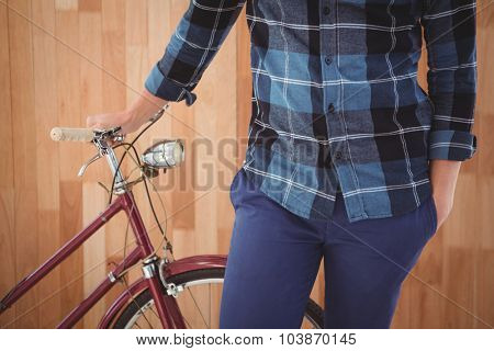 Mid section of hipster with bicycle standing against wooden wall