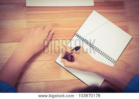 Cropped hand of businessman writing on spiral notebook at desk in office