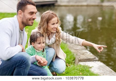 family, parenthood, leisure and people concept - happy mother, father and little girl walking in summer park near pond