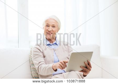 technology, age and people concept - happy senior woman with tablet pc computer at home