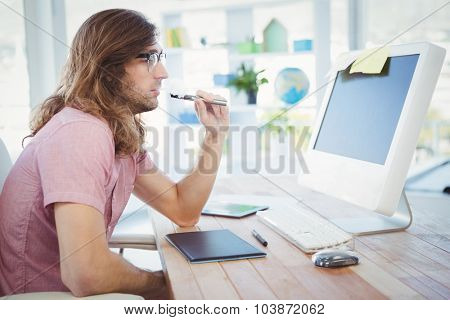 Side view of hipster smoking electronic cigarette at computer desk in office