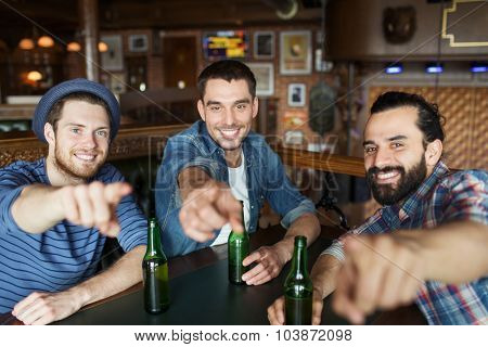 people, leisure, friendship and bachelor party concept - happy male friends drinking bottled beer and  and pointing on you at bar or pub