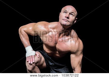 Bodybuilder exercising while lookign up against black background