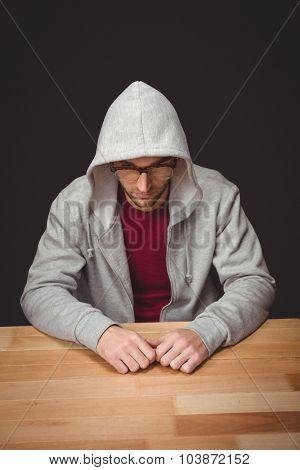High angle view of man with hooded shirt sitting at desk in office