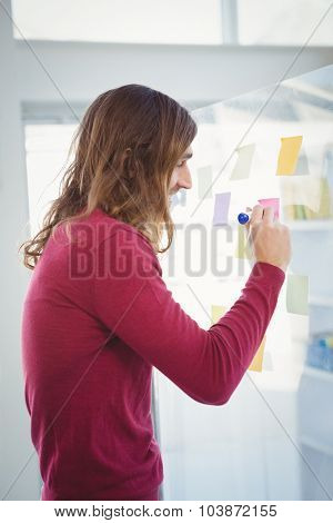 Side view of hipster writing on adhesive note stuck on glass in office