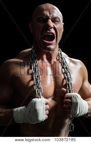 Aggressive fighter holding chain against black background