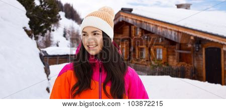 winter, leisure, clothing and people concept - happy young woman or teenage girl in winter clothes outdoors over wooden country house background and snow