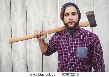 Portrait of hipster holding axe on shoulder against wooden fence