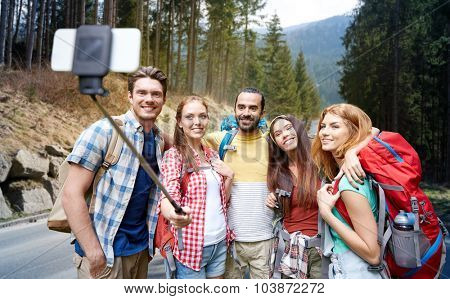 technology, travel, tourism, hike and people concept - group of smiling friends walking with backpacks taking picture by smartphone on selfie stick over woods and road background