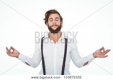 Hipster meditating with arms outstretched against white background