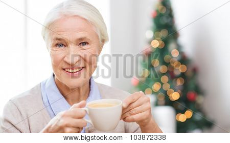 age, drink, holidays, winter and people concept - happy smiling senior woman with cup of coffee at home over living room and christmas tree background