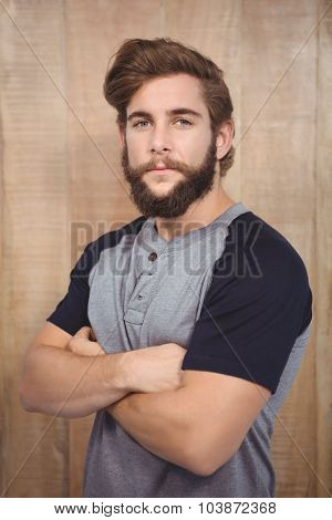 Portrait of confident hipster with arms crossed against wooden wall
