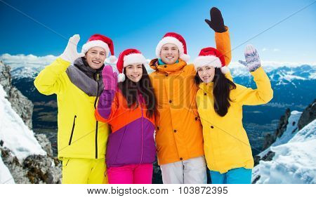 winter holidays, christmas, friendship and people concept - happy friends in santa hats and ski suits waving hands outdoors over snowy mountains background