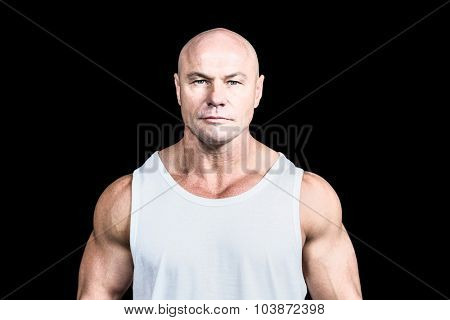 Portrait of confident bald man against black background
