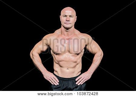 Portrait of confident bald man with hands on hip against black background