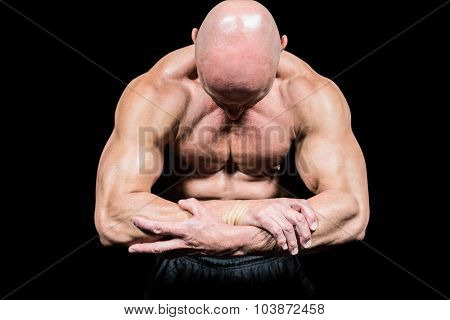 Bodybuilder flexing muscles while looking down against black background