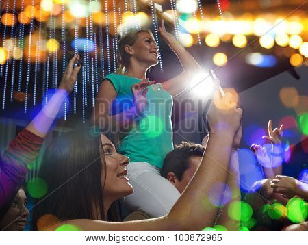 party, holidays, celebration, nightlife and people concept - smiling friends with smartphone taking picture and waving hands at concert in club