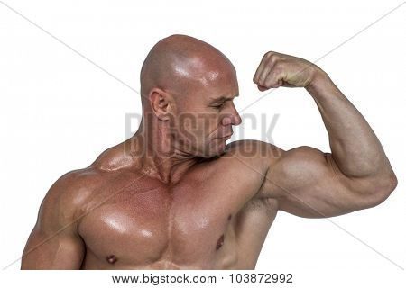 Muscular man looking at bicep against white background