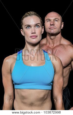 Muscular woman and man looking up against black background