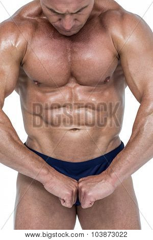 Powerful athlete flexing muscles against white background