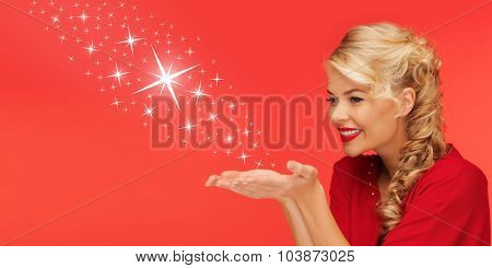 people, holidays, christmas, magic and winter concept - lovely woman in red clothes sending stars from on palms of her hands over red background