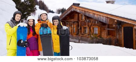 winter, leisure, extreme sport, friendship and people concept - happy friends in helmets with snowboards outdoors over wooden country house background and snow