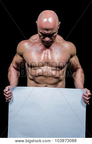 Muscular man holding blank paper while looking down against black background