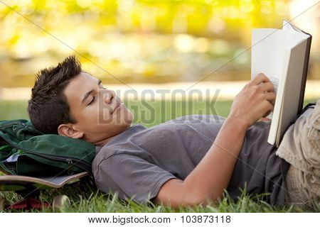 Student with skateboard and backpack reading in the grass