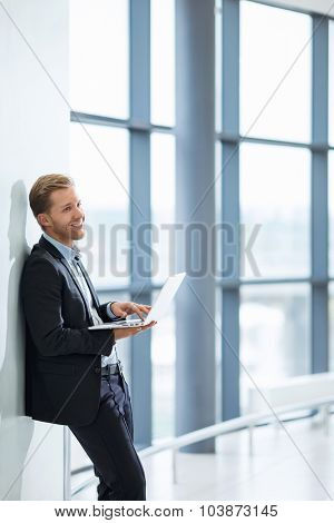 Young businessman with laptop indoors