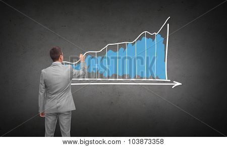 business, people, advertisement , information and office concept - businessman drawing diagram chart from back over dark gray concrete wall background