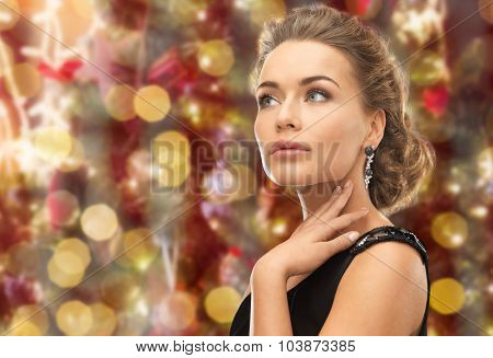 people, holidays, jewelry and glamour concept - beautiful woman wearing earrings over christmas lights background