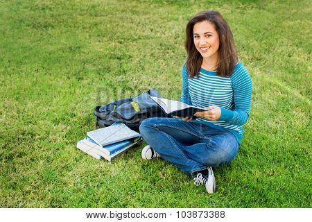 Young ethnic woman doing school work outside