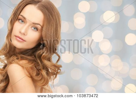 people, beauty, hair and skin care concept - beautiful woman with curly hairstyle over holidays lights background