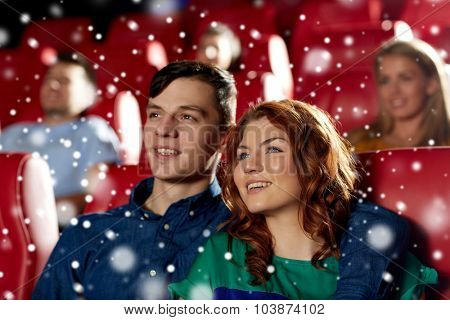 cinema, entertainment and people concept - happy couple watching movie and hugging in theater over snowflakes