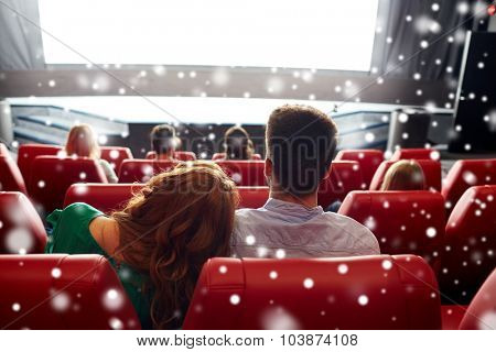 cinema, entertainment, leisure and people concept - happy couple watching movie in theater from back over snowflakes