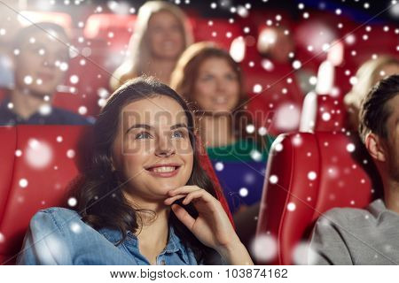 cinema, entertainment and people concept - happy woman watching comedy movie in theater over snowflakes